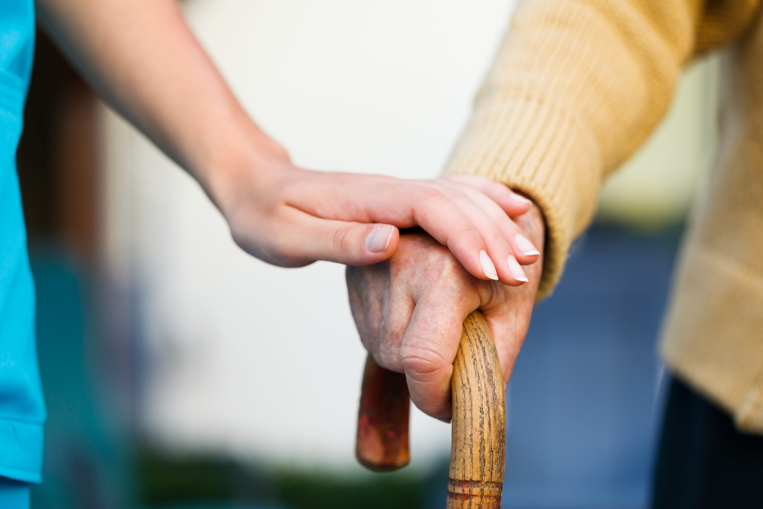 Doctor holding a senior patient's hand on a walking stick - a special medical care concept for Alzheimer 's syndrome.