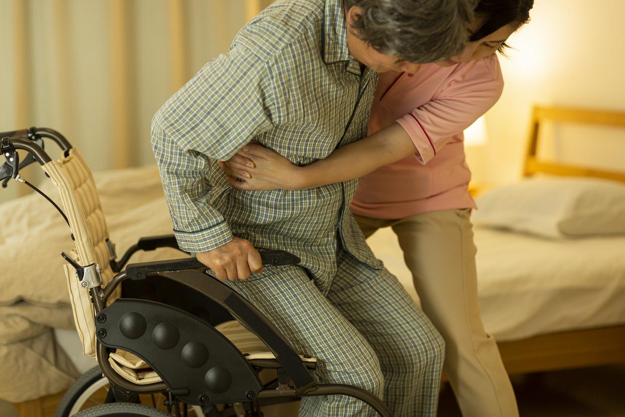 nurse helping older individual into wheelchair