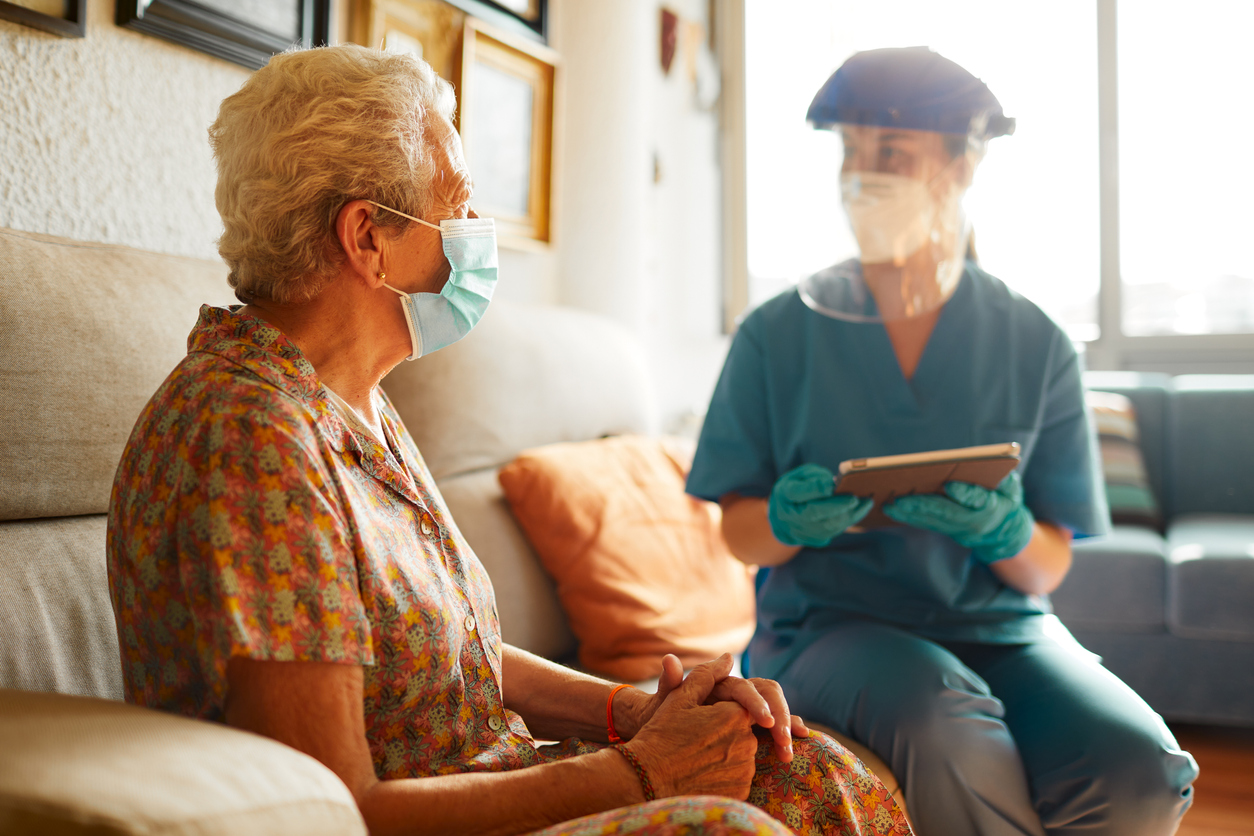 A female doctor visits a senior woman at the nursing home.